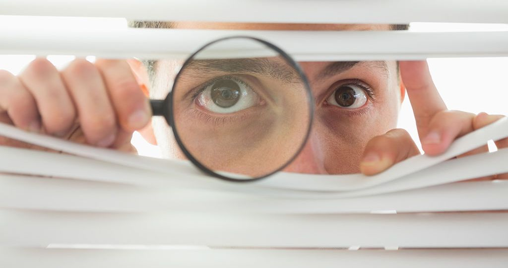 Male eyes spying through roller blind with loupe
