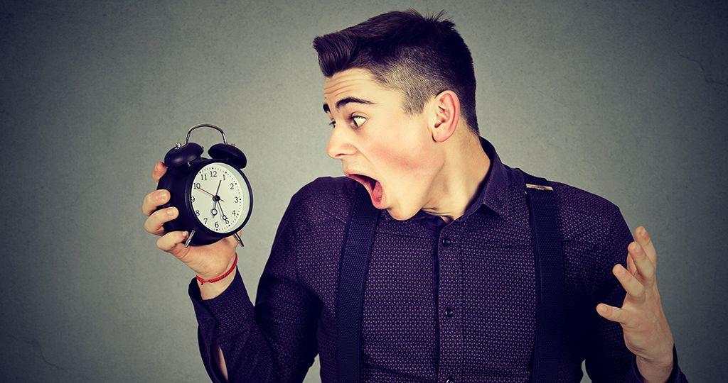 Anxious man looking at alarm clock. Time pressure