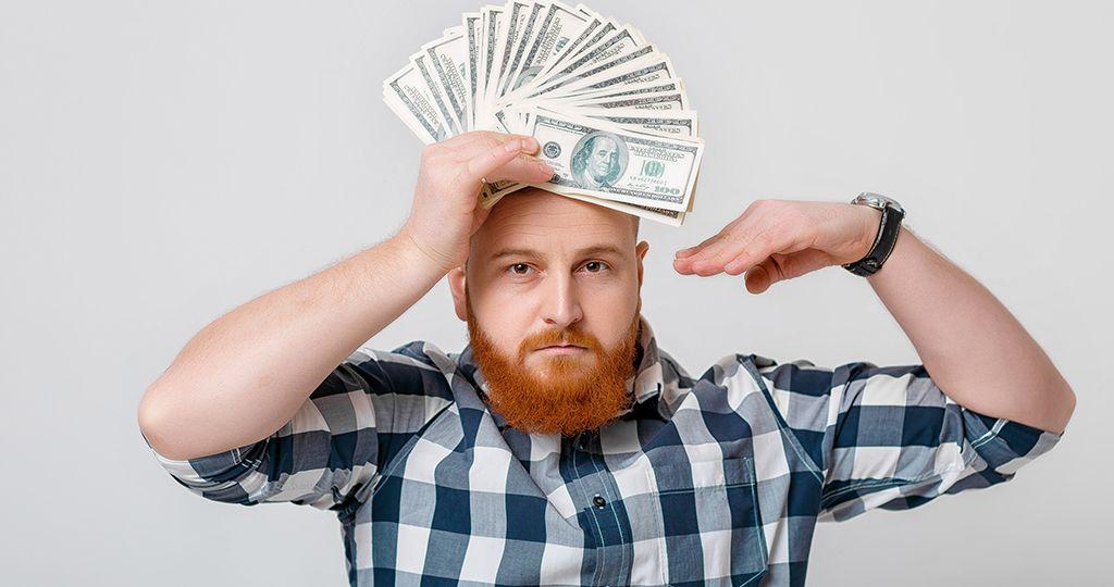 man with beard holding lot of hundred-dollar bills