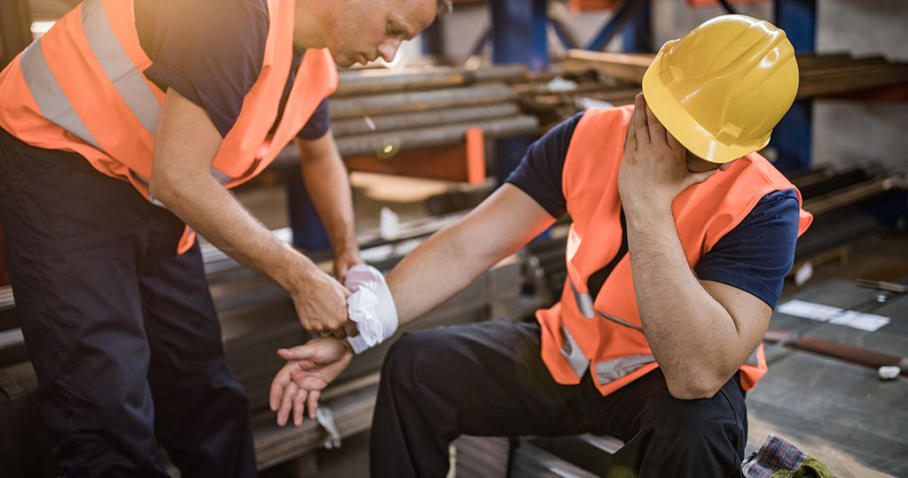 Manual worker assisting his colleague with physical injury in steel mill.